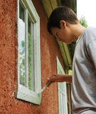 Boy staining window on the outside. Royalty Free Stock Photo