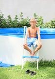 Boy on stairs to pool Stock Photos