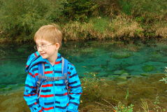 Boy stand by a pond. A boy stands by a water pond in the forest Royalty Free Stock Photos