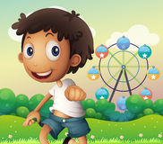 A boy standing across the ferris wheel Stock Image