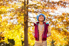 Boy standing against autumn trees at park Stock Photos