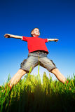 Boy standing against the blue sky. Boy with outstretched arms standing against the blue sky background Stock Photography