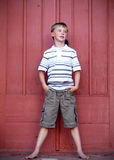 Boy Standing Against Red Wall - Vertical Royalty Free Stock Photography