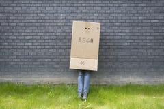 Boy standing against a wall. Shy teenage boy standing against a wall with a cardboard box over his head stock photo