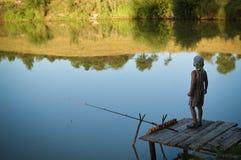 Boy standing alone on riverside pontoon in Stock Image