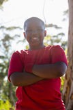 Boy standing with arms crossed during obstacle course training Royalty Free Stock Photo
