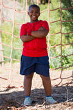 Boy standing with arms crossed during obstacle course training Royalty Free Stock Image