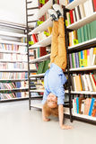 Boy standing on arms upside down leaning at shelf Stock Images