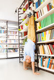 Boy standing on arms upside down in library Royalty Free Stock Images
