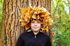 Boy standing in autumn park on a background of trees. At the head of woven wreath of autumn leaves royalty free stock photo