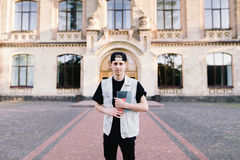 Boy standing on a background in front of his university and holding a student notebook. A handsome young boy standing on a background in front of his university Royalty Free Stock Photos