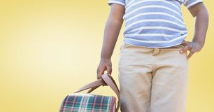 Boy standing with bag against yellow background. Mid section of boy standing with bag against yellow background Royalty Free Stock Photography