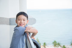 Boy standing at balcony and smiles Royalty Free Stock Images