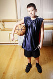 Boy standing with basketball Royalty Free Stock Images