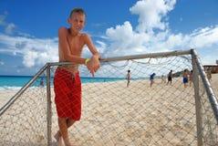 Boy standing at beach goalpost Stock Photography