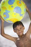 Boy (7-9) standing on beach, holding green beach ball above head, smiling, portrait (tilt) royalty free stock images