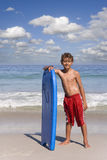 Boy standing on beach near ocean with body board Stock Photography