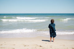 Boy standing on the beach Stock Photos