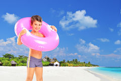 Boy standing on beach with swimming ring stock image