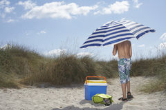 Boy Standing On Beach With Umbrella Royalty Free Stock Photo