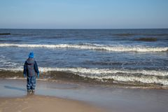 A boy is standing on the beach watching the sea Stock Image
