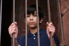 Boy standing behind bars Stock Photos