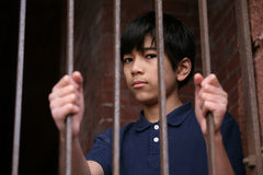 Boy standing behind bars Royalty Free Stock Photo