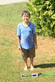 Boy standing behind sprinkler. Barefoot little boy - kid in blue t-shirt and brown shorts standing behind splashing sprinkler and soaking wet royalty free stock image