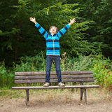 Boy standing on a bench in a forest Royalty Free Stock Photo