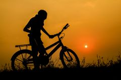 Boy and standing bicycle silhouette with sunset light. Background. The Boy and standing bicycle silhouette with sunset light. Background stock photo