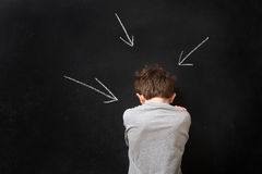 Boy standing at a blackboard with arrows Stock Photography