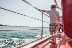 Boy standing on boat deck on sunny day Stock Photos