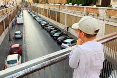 Boy standing on bridge, holding hands on railing Royalty Free Stock Photos