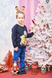 The boy is standing by the Christmas tree Stock Images