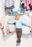 Boy standing among clothes on hangers and shelf Royalty Free Stock Images