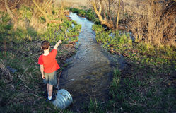Boy Standing on Culvert by Stream Stock Photos