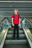 Boy standing on an escalator Stock Photo