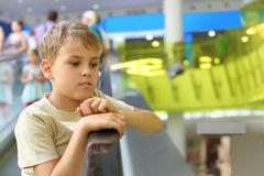 Boy standing on escalator and moving up Stock Photos