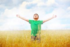 A boy standing in a field of wheat against cloudy. A boy standing in a field of wheat in green T-shirt and spred arms against cloudy sky background stock photo