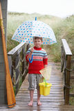 Boy standing on footbridge with umbrella Royalty Free Stock Images