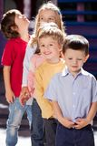 Boy Standing With Friends In A Row At Kindergarten. Portrait of cute boy standing with friends in a row at kindergarten Stock Photos