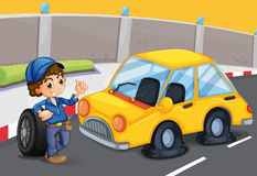 A boy standing in front of a car with a flat tire Royalty Free Stock Image