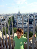 Boy standing in front of eiffel tower. Boy standing at the top of arc de triumph with eiffel tower behind Royalty Free Stock Photography