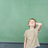 Boy standing in front of empty chalkboard Stock Photos