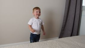 The boy is standing in front of the parents` bed and having fun with their parents stock video footage
