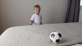 The boy is standing in front of the parents` bed and having fun with their parents stock footage