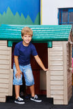 Boy standing in front of playhouse Royalty Free Stock Images