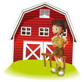 A boy standing in front of the red barnhouse Stock Images