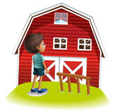 A boy standing in front of the red farmhouse Royalty Free Stock Photos