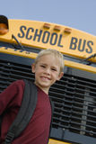 Boy Standing In Front Of School Bus Royalty Free Stock Photography